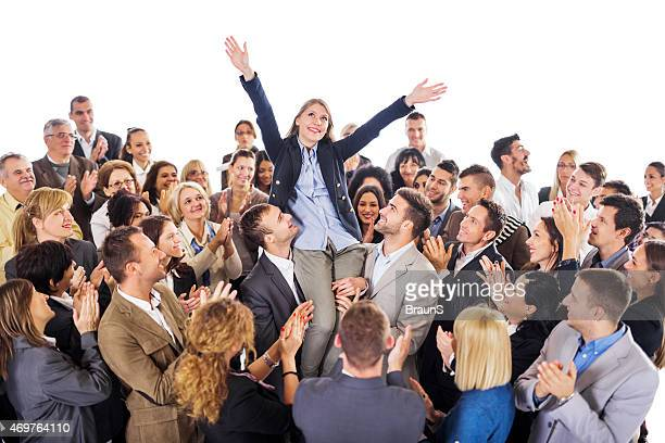 Crowd of business people congratulating their colleague on her success.