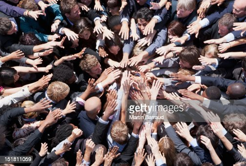 Crowd of business people extending hands in huddle : Stock Photo