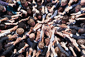 Crowd of business people extending hands in huddle
