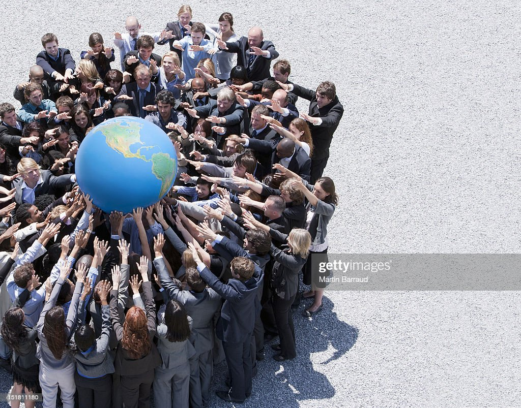 Crowd of business people in huddle reaching for globe : Stock Photo