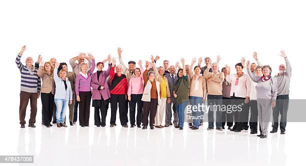 Crowd of cheerful senior men and women waving.