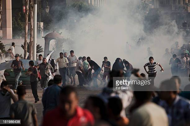 A crowd of Egyptian protesters flee from a heavy barrage of tear gas fired by riot police during clashes near the United States Embassy on the Nile...