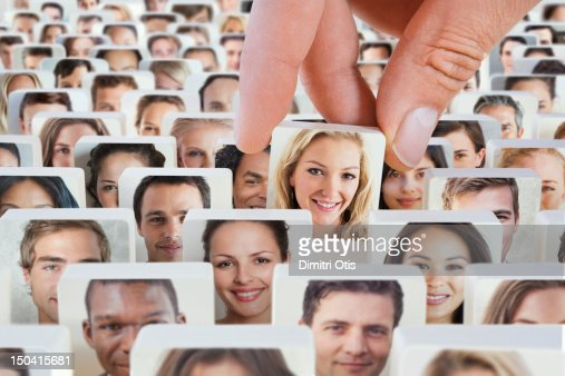 Crowd of faces on discs, a woman being lifted out : Stock Photo