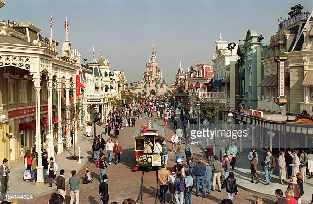 A crowd of guests walk down Eurodisney main street with the sleeping beauty castle as background after having attended the general rehearsal of the...