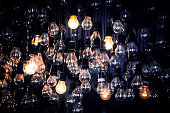 Crowd of Hanging Light Bulbs with few turned on. Concept for idea, crowd of people with few exeptions, light in dark.