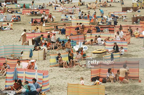 A crowd of holidaymakers use windbreaks to make the most of a British holiday on the beach at Perranporth Cornwall circa 1970