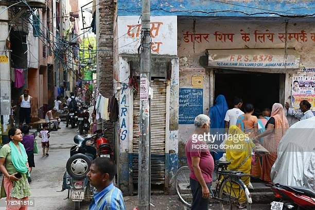 A crowd of Indian residents gather outside the Fair Price Shop a government food dispensary owned by Brij Kishore in the northern district of...