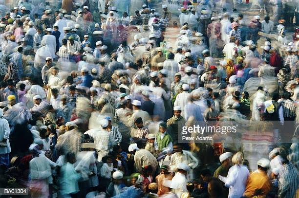 Crowd of Islamic worshippers at mosque, elevated view (blurred motion)