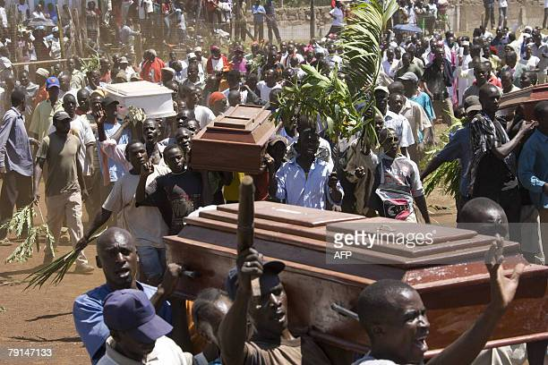 A crowd of Kenyans carry the coffins of six victims of postelection violence in the Western Kenyan town of Kisumu during a mass funeral 21 January...