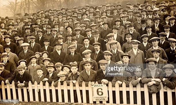 A crowd of men and boys all wearing hats waiting for the football match between Brighton Hove Albion and Crystal Palace at the Goldstone Ground in...