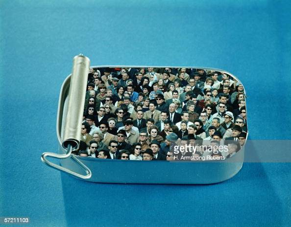 Crowd of men and women packed inside open sardine tin