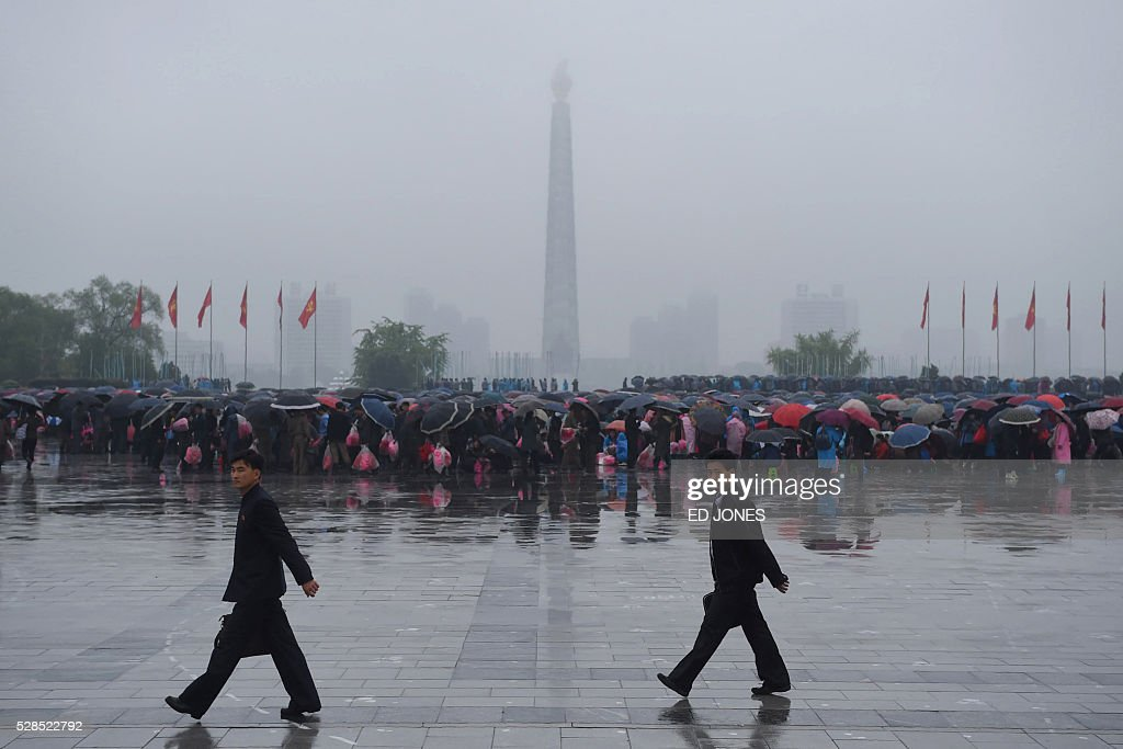 A crowd of people are seen on Kim Il-Sung Square before the Juche tower as rain falls in Pyongyang on May 6, 2016. North Korea will on May 6 launch its highest-level ruling party meeting in almost 40 years, with delegates set to heap praise on its nuclear arsenal as a 'precious sword' amid fears of a fresh atomic test. / AFP / Ed Jones