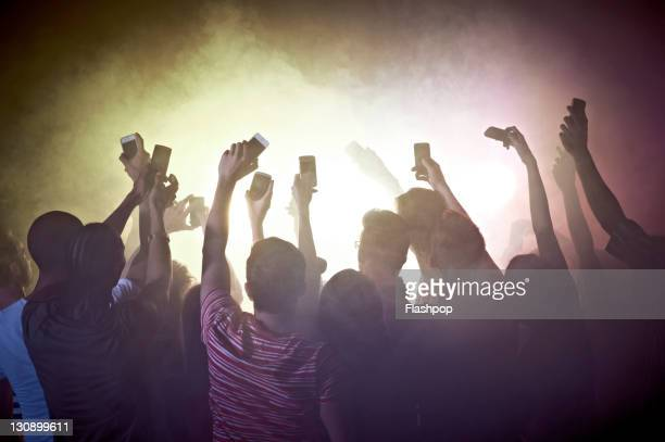 Crowd of people at concert using mobile phones