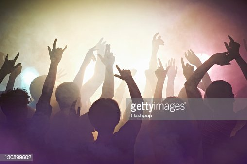 Crowd of people at concert waving arms in the air : Stock Photo