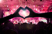 crowd of people at during a concert with a heart shaped hand shadow male and female