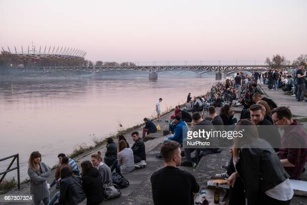 Crowd of people at Vistula known as Wisla river in Warsaw with a view of Polish National Stadium Banks of river became place where Polish law allow...