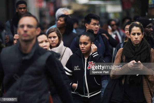 A crowd of people cross the street in midtown Manhattan on October 31 2011 in New York City Around the world countries marked the global population...