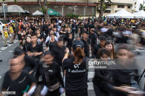 A crowd of people flow in past a volunteer at one of the entrances to the periphery of the Grand Palace in Bangkok on October 5 on the last day that...