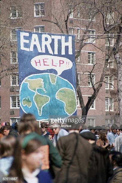 A crowd of people gather near a large poster that shows a speach bubble from planet Earth that reads 'Help' on the occaision of the first Earth Day...