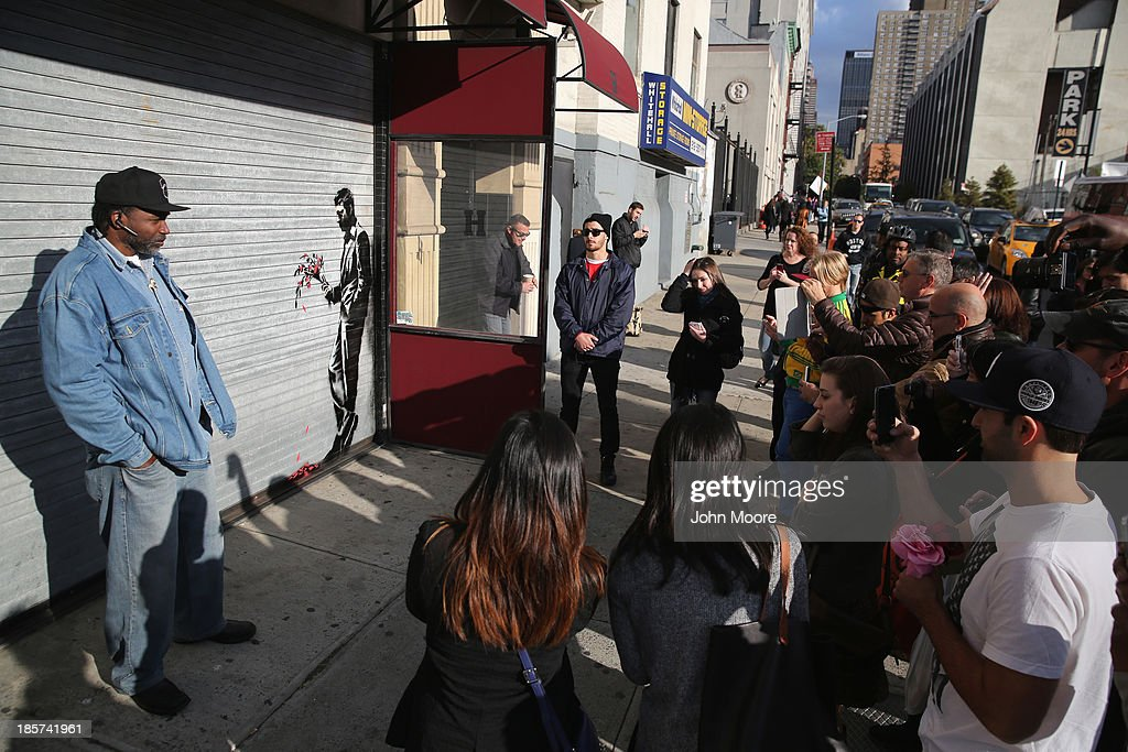 A crowd of people gather to see a painting by British street artist Banksy on a roll-down security gate covering the main entrance to Larry Flint's Hustler Club on October 24, 2013 in the Hell's Kitchen neighborhood of New York City. On Banksy's website a caption for the work reads, 'Waiting in vain...at the door of the club.'