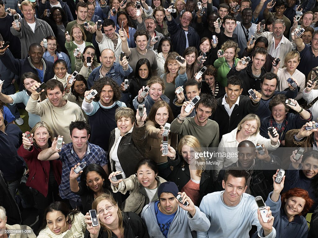 Crowd of people holding mobile phones aloft, portrait, elevated view : Stock Photo