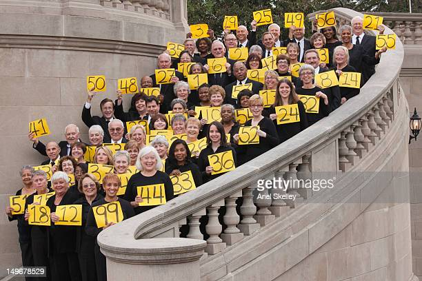 Crowd of people holding numbered signs on stairs