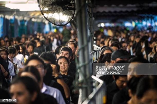 A crowd of people line up under canopies set up in the periphery of the Grand Palace in Bangkok on the last day that Thai authorities allow people to...