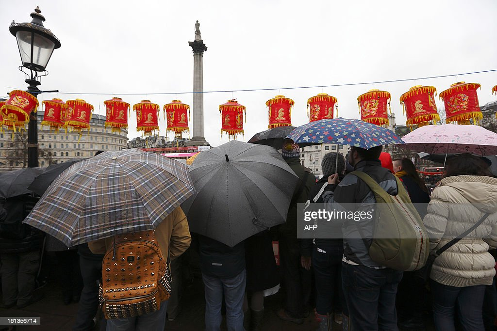 A crowd of people shelter from the rain under umbrellas as they stand and watch performers in Trafalgar Square celebrating Chinese New Year in central London on February 10, 2013. Chinese communities world wide traditionally welcomed in the 'Year of the Snake'.