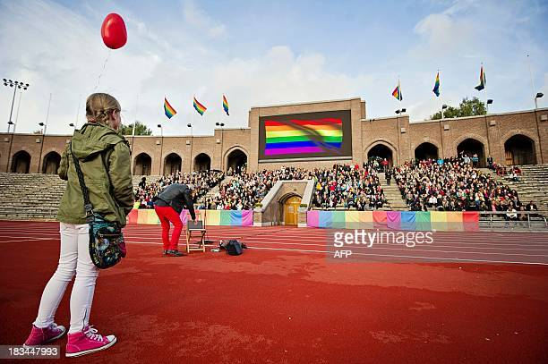 A crowd of people sing the Russian National Anthem at the Stockholm Olympic Stadium on October 6 2013 while raising rainbow flags in solidarity with...