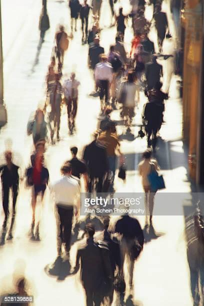Crowd of People Strolling down City Sidewalk