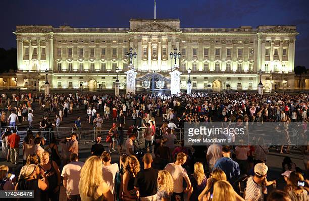 A crowd of people take photos of the easel that officially announced the birth of the son of The Duke and Duchess of Cambridge at Buckingham Palace...