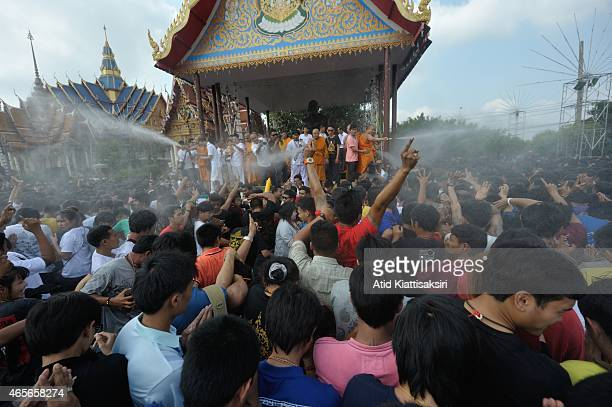 A crowd of people try to reach for holy water being sprayed by a Buddhist monk in front of an image of Abbot Pern a master of magical tattoo former...
