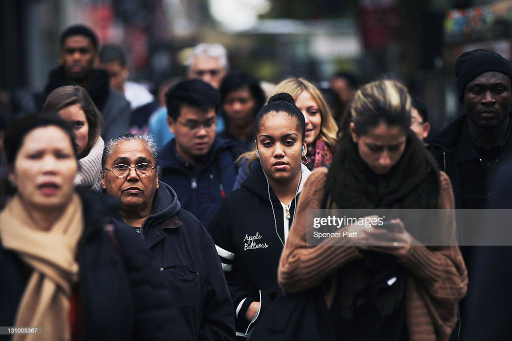 A crowd of people wait to cross the street in midtown Manhattan on October 31 2011 in New York City Around the world countries marked the global...