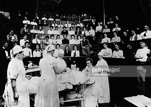 A crowd of people watch surgeons perform an operation in an operating theatre