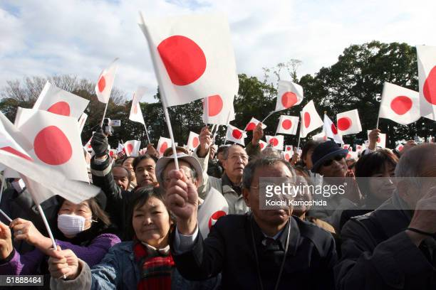 A crowd of people wave Japanese flags and cheer during a ceremony to celebrate Emperor Akihito's 71st birthday at the Imperial Palace December 23...