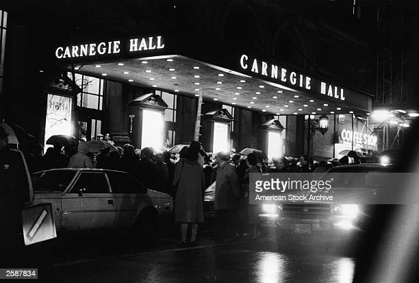 A crowd of people with umbrellas stand in front of Carnegie Hall at night New York City circa 1975