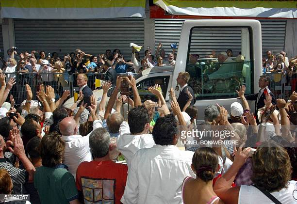 A crowd of pilgrims welcomes Pope John Paul II in his 'papamobile' 14 August 2004 at the pope's arrival in Lourdes The town is bedecked in the yellow...
