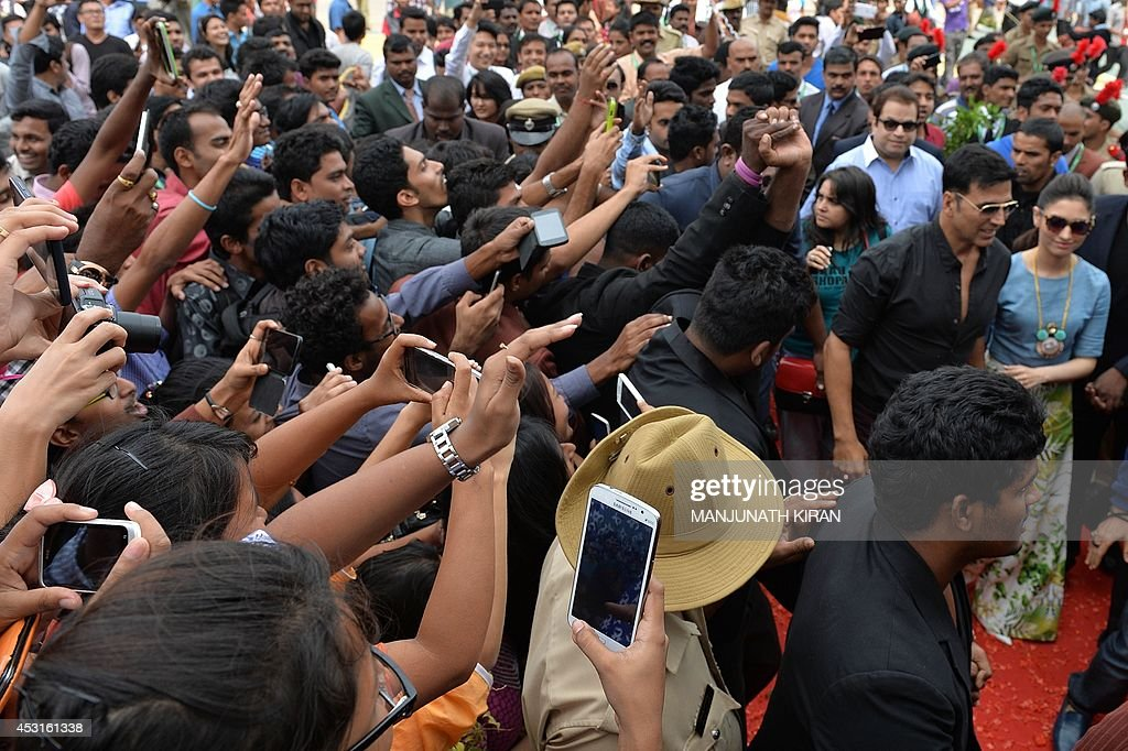 A crowd of private college students gather and take photographs of Indian Bollywood actors Akshay Kumar (2R) and Tamannaah Bhatia (R) as they arrive for the promotion of their latest movie 'Entertainment' in Bangalore on August 4, 2014. AFP PHOTO/Manjunath KIRAN