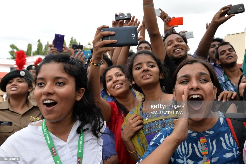 A crowd of private college students gather and take photographs of Indian Bollywood actors Akshay Kumar and Tamannaah Bhatia as they arrive for the promotion of their latest movie 'Entertainment' in Bangalore on August 4, 2014. AFP PHOTO/Manjunath KIRAN