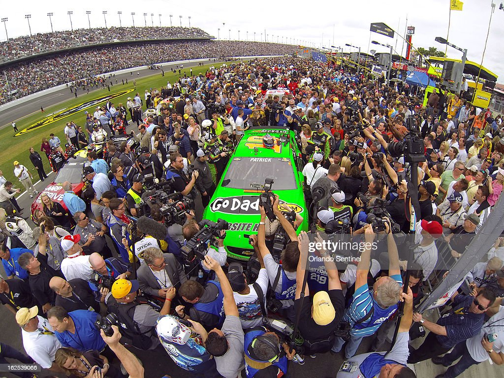 A crowd of race officials, fans and media jam pit row around Danica Patricks' Chevrolet before the start of the Daytona 500 at Daytona International Speedway in Daytona Beach, Florida, Sunday, February 24, 2013.