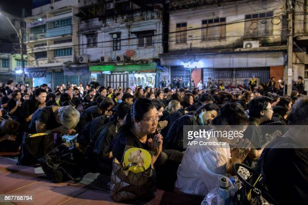 A crowd of residents of Bangkok bow down as they see the the royal vehicles pass by in a procession that took the relics of the late Thai king...