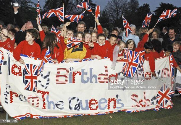 Crowd of schoolchildren cheering with birthday greetings banner and Union Jack flags gather to welcome the Queen as she arrives for her 80th birthday...