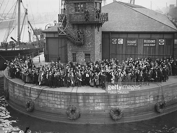 A crowd of Scottish emigrants waits for a boat at a wharf in Glasgow