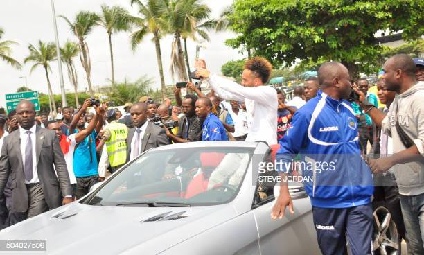 A crowd of supporters welcomes newlycrowned African Player of the Year Borussia Dortmund football player PierreEmerick Aubameyang holding his trophy...
