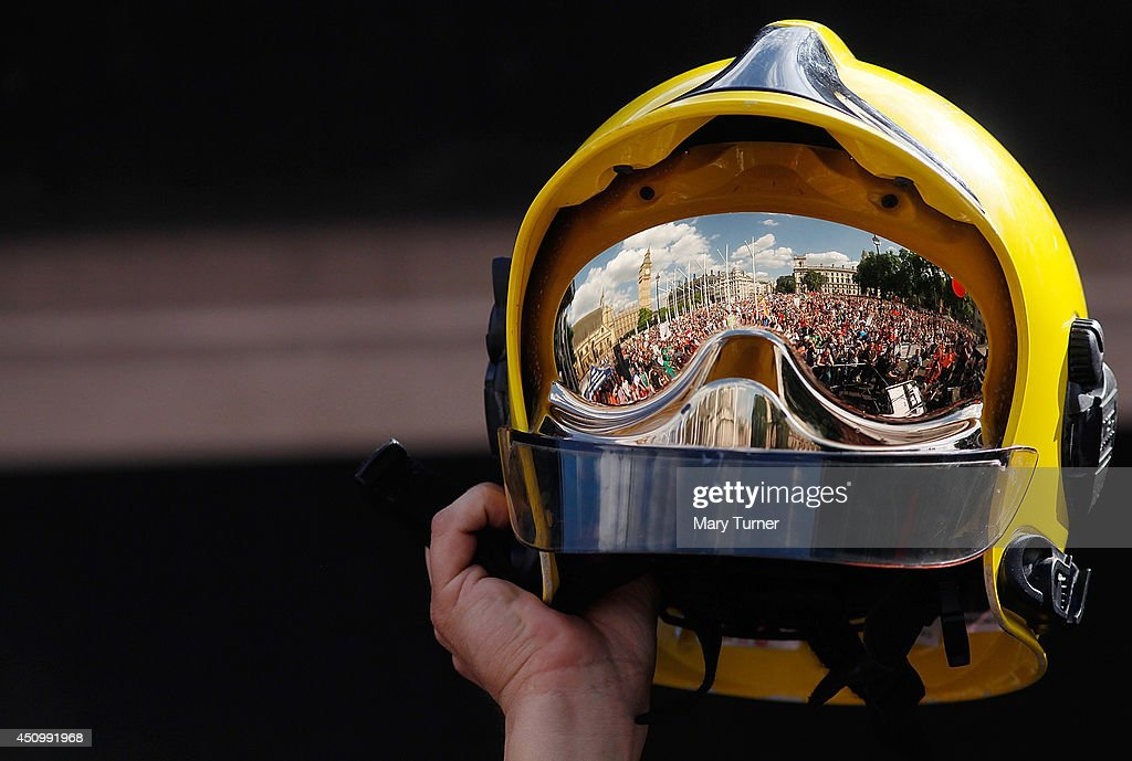 A crowd of thousands of demonstrators are reflected in a firefighter's helmet held up on stage in front of the gathering in Parliament Square, on June 21, 2014 in London, England. The crowd marched from Oxford Circus to Parliament Square to voice their opposition to government austerity cuts.