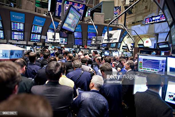 A crowd of traders stand near the post where Berkshire Hathaway is traded after the close of trading on the floor of the New York Stock Exchange in...