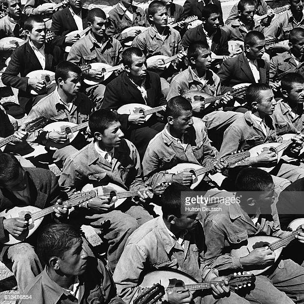 A crowd of Turkish teenagers playing their national instrument the saz during a break from their work on a village institute farm They have been sent...