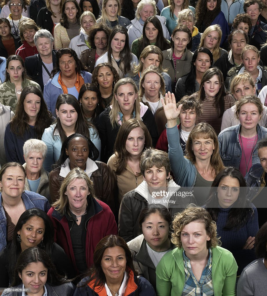 Crowd of women looking up, one woman raising hand, smiling, portrait : Stock Photo