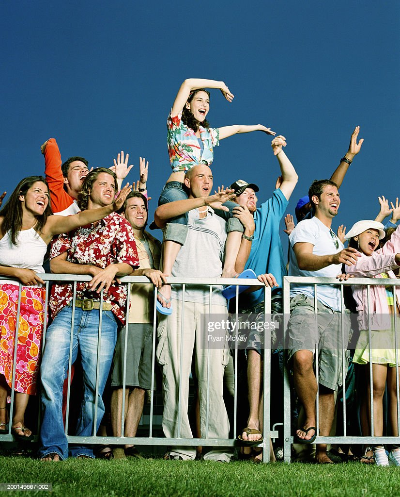 Crowd of young adults at outdoor event, cheering : Stock Photo