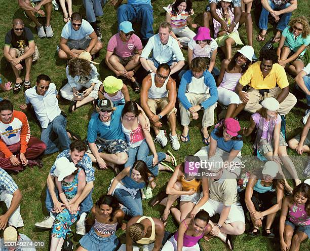 Crowd of young adults sitting on grass, elevated view